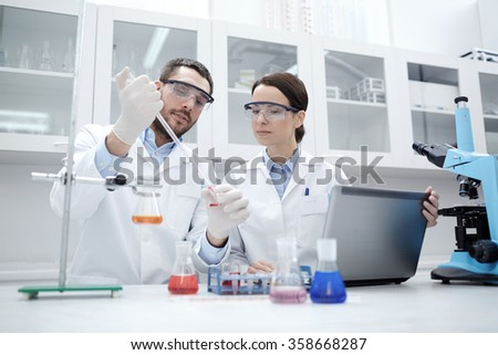 young scientists making test or research in lab - stock photo