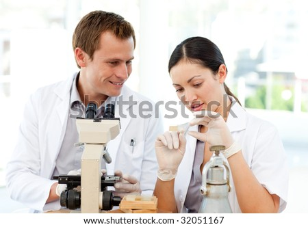 Young scientists studying a slide under a microscope - stock photo