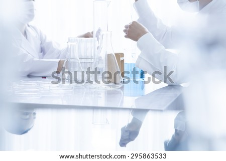 Young scientists with pipette and flask making test or research in clinical laboratory - stock photo