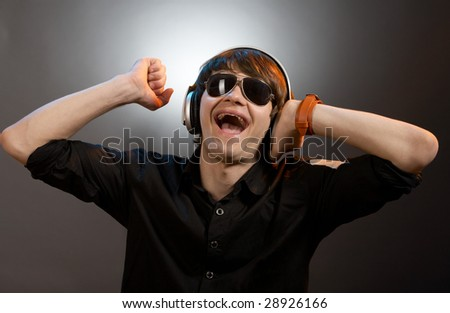 young screaming caucasian dj with headphones over grey background - stock photo