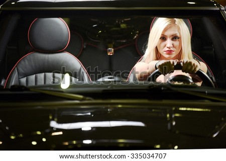 Young, sensual and serious blonde girl driving the car in the night. - stock photo