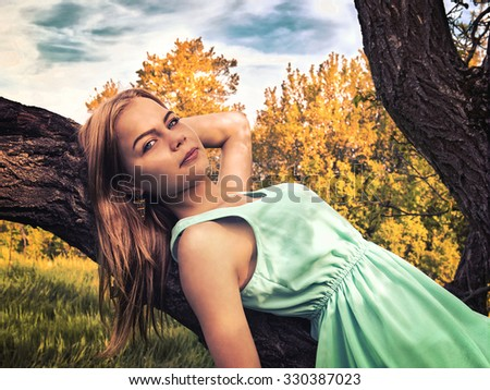 Young sensual blonde girl lying on a tree branch - stock photo