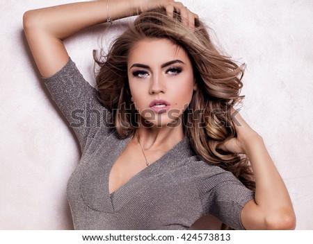Young sensual blonde woman posing in silver lingerie, slim body. Studio shot. - stock photo