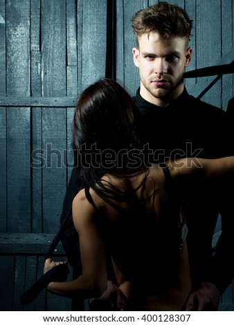 Young sensual couple of stylish man in shirt and pretty sexy topless woman with back embracing lover indoor on wooden background, vertical picture - stock photo