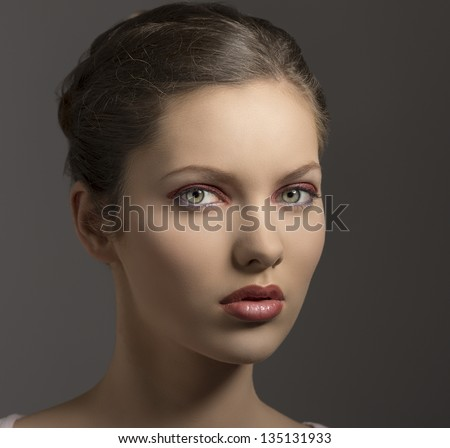 young sensual lady with purple make-up, perfect skin, brown hair looking in camera on gray background - stock photo