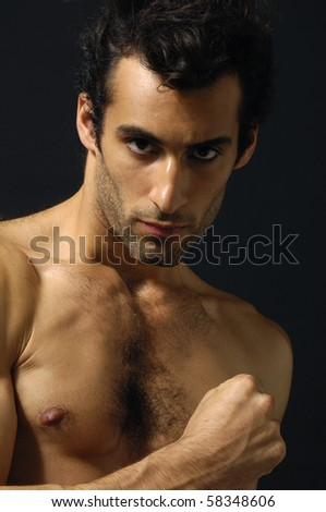 young sensual man on a black background - stock photo