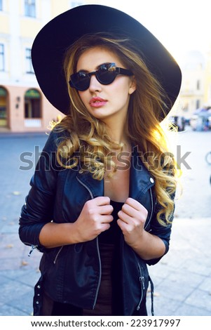 Young sensual pretty stylish blonde girl, with a,axing long curled hairs, wearing elegant retro hat, vintage sunglasses and black leather jacket, bright evening fall sunlight. - stock photo