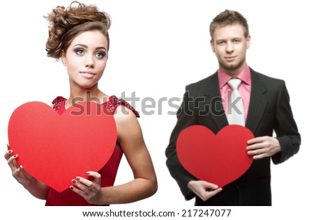 young sensual woman and handsome man holding red heart isolated on white background - stock photo