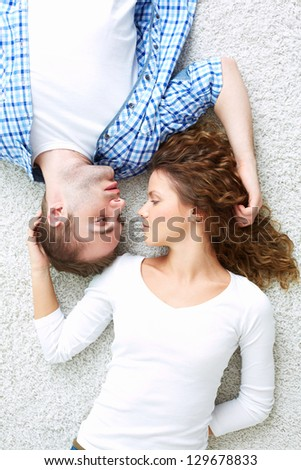 Young serene couple lying on the floor and looking at one another - stock photo