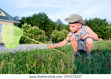 Young Serious Boy with Bug Net Exploring Long Grass on Lawn in front of Home - stock photo