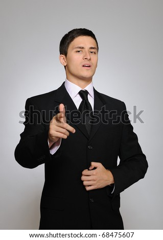 Young serious business man in black suit and tie. gray background - stock photo