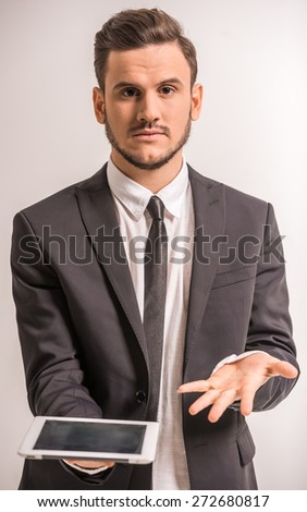 Young serious businessman is holding  a tablet on grey background. - stock photo