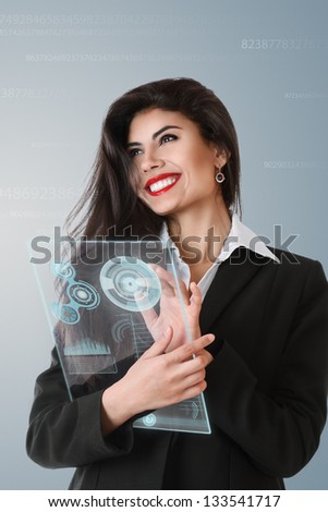 Young serious businesswoman working on modern touch screen - stock photo