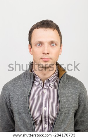Young serious Caucasian man in casual clothing, studio portrait over white background - stock photo