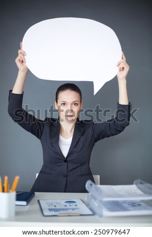 Young serious female with paper speech bubble - stock photo