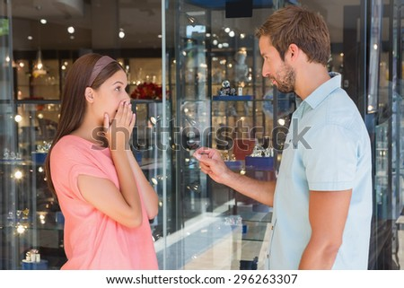 Young serious man giving jewellery to a surprised woman in front of the jewellery store - stock photo