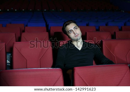 Young serious man in black watches movie in big cinema theater. - stock photo