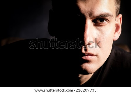 Young serious man on black background in low key - stock photo