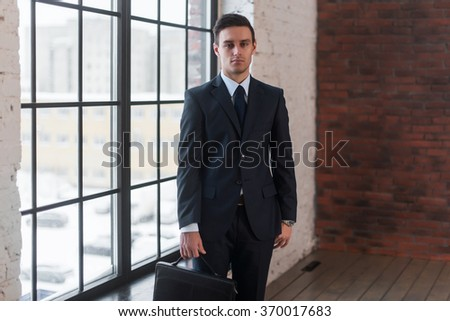 Young serious man standing near office window. Manager director boss entrepreneur employer. - stock photo