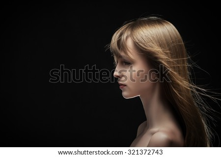 young serious sad woman profile on black - stock photo