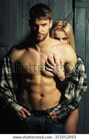 Young sexual couple of handsome serious man in checkered shirt with bare muscular chest standing before pretty blonde woman embracing and touching breast in studio, vertical picture - stock photo