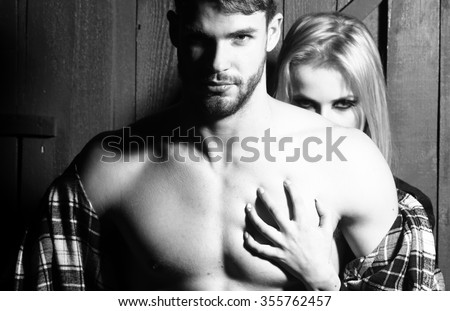 Young sexual couple of handsome serious man in checkered shirt with bare muscular chest standing before pretty blonde woman embracing and touching breast in studio, horizontal picture - stock photo