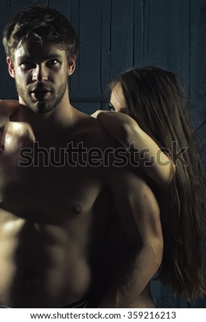 Young sexual passionale sensual couple of attractive woman with beautiful naked body and long hair embracing handsome muscular man standing close to each other indoor, vertical photo - stock photo