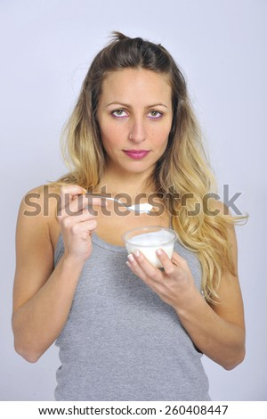 young sexy and attractive blond hair girl with spoon happy and fit eating natural cream yogurt in diet healthy nutrition and fitness concept isolated on clear background - stock photo