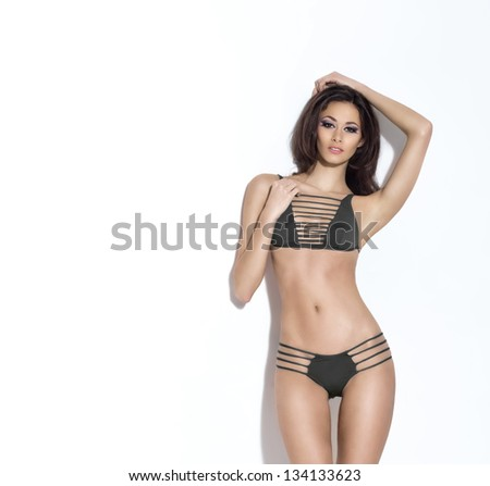 Young, sexy and beautiful woman in swimsuit over white background - stock photo