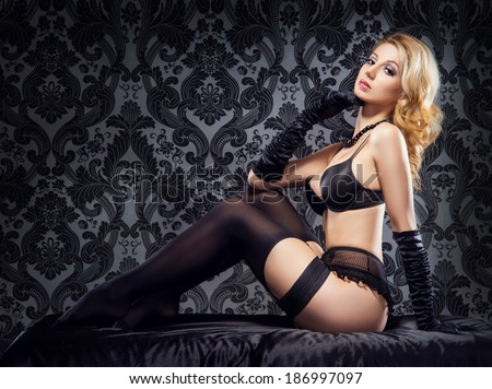 Young, sexy and beautiful woman in underwear in the bed over retro background. - stock photo