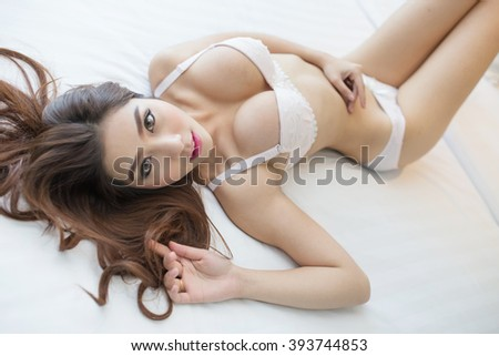 Young sexy asian girl in underwear posing or lying on her bed - stock photo