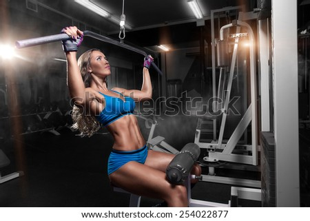 Young sexy athlete girl lifts in the gym - stock photo