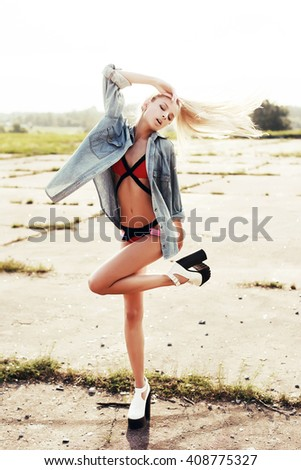 Young sexy blonde beautiful woman posing outdoor on the street in fashion pose dressed in red bikini and jeans shirt  - stock photo