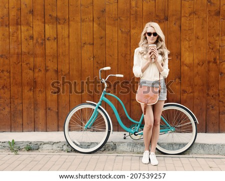 Young sexy blonde girl with long hair with brown vintage bag in sunglasses standing near vintage green bicycle and holding a cup of coffee, have fun and good mood looking in camera and smiling - stock photo