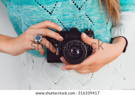 Young sexy blonde woman posing on white wall with professional camera, wearing leater jacket, swag accessorize,hipster outfit , holding vintage camera, Lifestyle portrait bright toned colors.  - stock photo