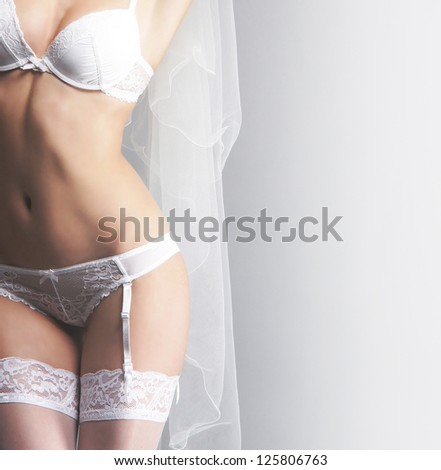 Young sexy bride in erotic lingerie over grey background - stock photo