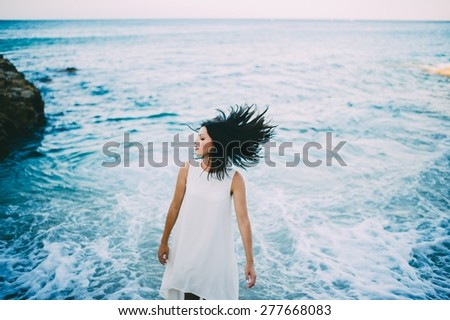 Young sexy brunette in blue water in a white dress on the beach in Greece - stock photo