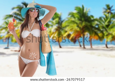 Young sexy brunette in white swimsuit on tropical beach. - stock photo