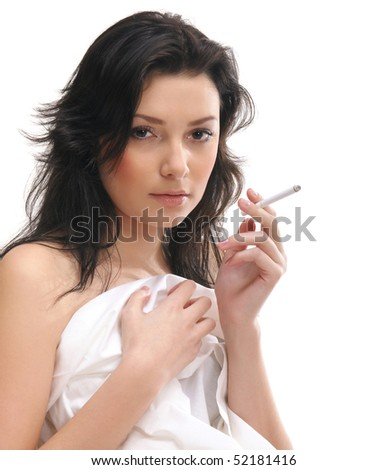Young sexy brunette smokes in the bed - stock photo