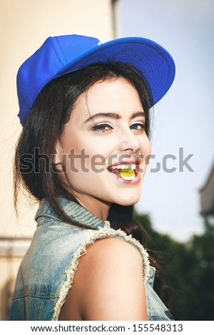 Young sexy brunette woman biting gelatin candy and smiling. - stock photo