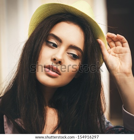 Young sexy brunette woman closeup portrait. Stylish woman posing on the street with interested look and green hat on her head. - stock photo