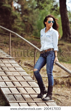 Young sexy brunette woman in sunglasses - stock photo