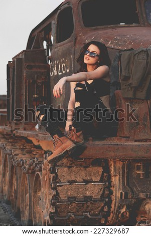 Young sexy brunette woman in sunglasses posing on the old tank at sunset.Fashion colors.  - stock photo