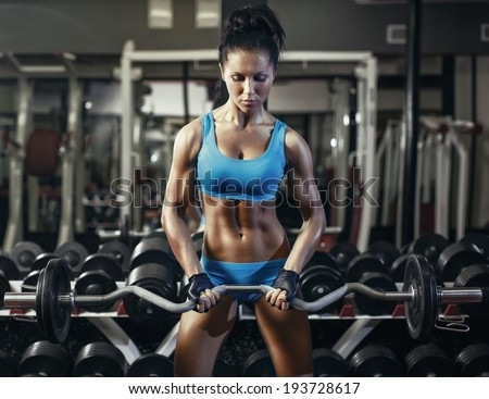 Young sexy brunette woman in the gym doing biceps exercise with barbell. Fitness girl in gym in a blue sport wear - stock photo