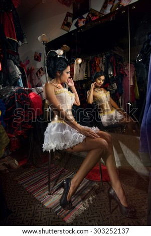 Young sexy cabaret female dancer in dressing room, backstage - stock photo