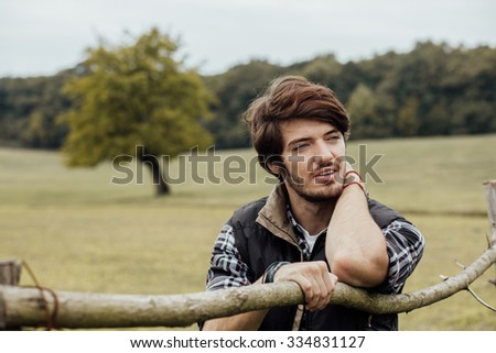 young sexy country boy next to a wooden fence, standing outside in nature - stock photo