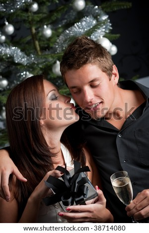 Young sexy couple kissing in front of Christmas tree, woman unpacking present - stock photo