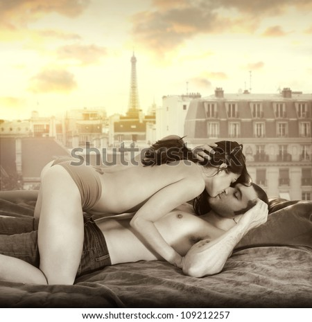 Young sexy couple making passionate love in bed against window overlooking Paris skyline with retro vintage sepia tones - stock photo