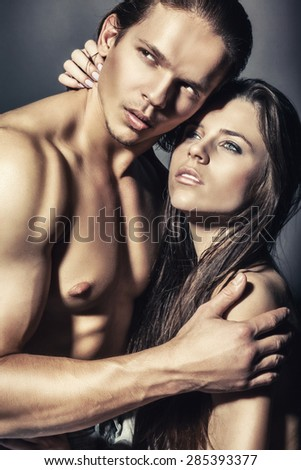 Young sexy couple on a dark background - stock photo