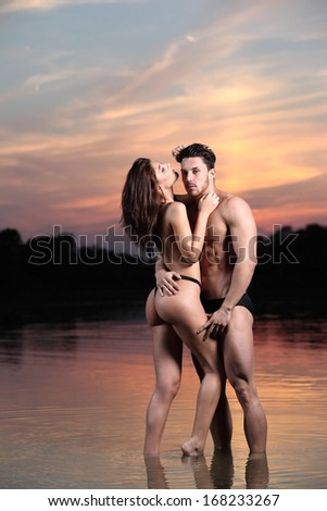Young sexy couple on beach with sun rising in background - stock photo